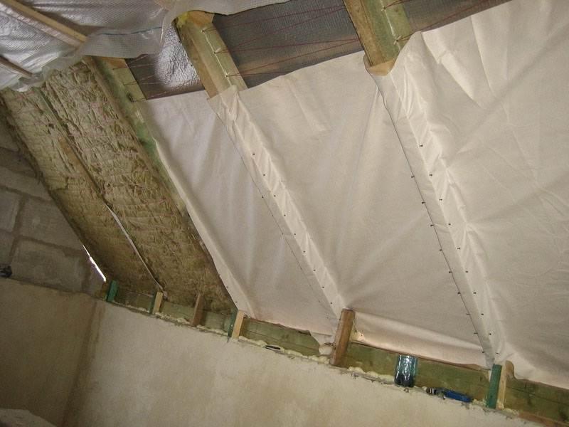 После завершения утепления, нужно позаботится о перекрытии утепляющего материала. В донном случаи часто используют тканевые материалы и монтажные скобы.
